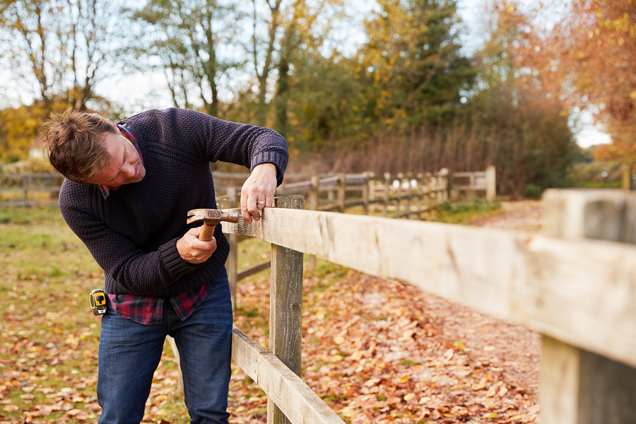 professional fence worker working on wooden fences repair