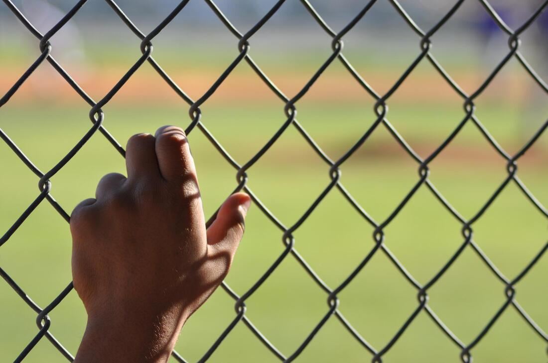 close up hand grabbing chain link fences